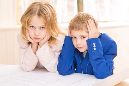 grumpy: Grumpy faces. Boy and girl are both mockingly frowning while leaning on the desk. Stock Photo