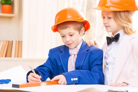 protective helmets: Little architects. Little boy and girl are wearing protective helmets and working on construction plans