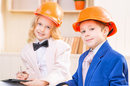 protective helmets: Little professionals. Boy and girl are smiling while wearing orange protective helmets.