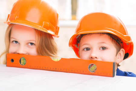 protective helmets: Behind the ruler. Little kids are wearing protective helmets and hiding behind the ruler. Stock Photo