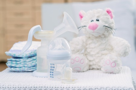 feeding bottle: Waiting for child. Close up of feeding bottle, nipple and toy standing on the surface of table Stock Photo