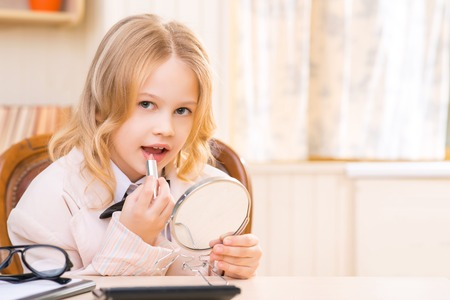 putting lipstick: Looking lovely. Pretty little girl is sitting at the desk and putting lipstick on.