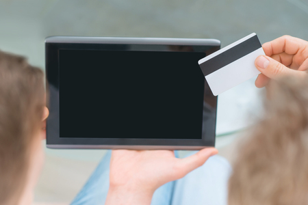 bloke: Pay it online. Close up of tablet and credit card in hands of father and his adult son holding them while sitting on the sofa
