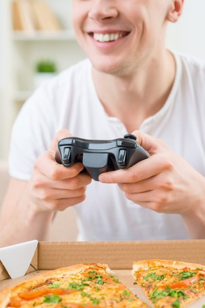 bloke: Having fun. Cheerful delighted smiling man holding video game console and playing while expressing gladness