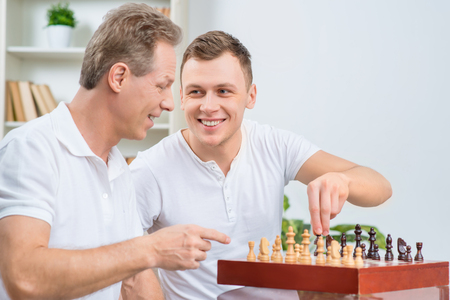 grand son: Adapt grand masters. Pleasant handsome positive adult son holding chessman while playing chess with his father