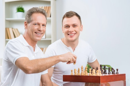 bloke: Good move. Cheerful smiling father holding chessman and playing with his adult son chess while sitting on the sofa Stock Photo