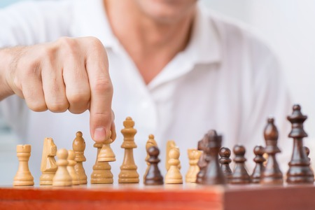 pawn adult: Involved in game. Selective focus of pawn in hands of nice man holding it and making a move while playing chess Stock Photo