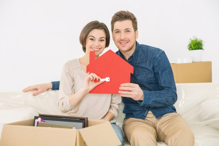 newly weds: Dreams come true. Happy loving young couple holding little red house and key from their new flat while sitting on the sofa Stock Photo