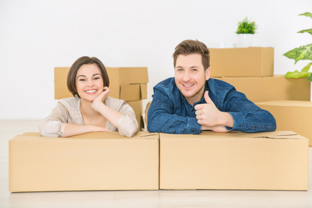 newly weds: Life is great. Upbeat smiling young couple sitting on the floor and leaning on the boxes while feeling glad