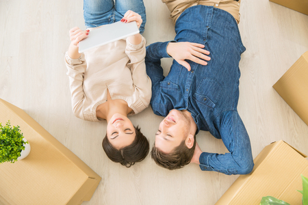 newly weds: Great time. Top view of positive happy smiling couple holding laptop and lying on the floor while feeling delighted