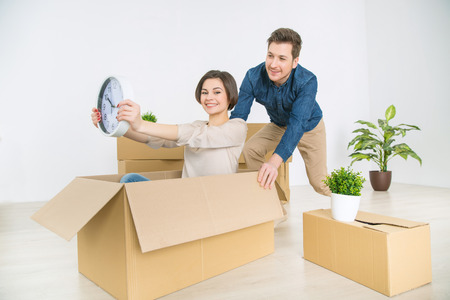 some: Get some drive. Cheerful smiling woman sitting in  a big box and holding a clock while her husband pushing it