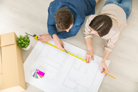newly weds: Let it be true. Top view of happy loving young couple holding pencils and drawing plan of their flat while lying on the floor