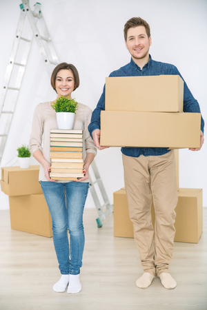 newly weds: Forever together. Happy smiling positive couple holding boxes and books while being involved in removal and expressing gladness Stock Photo