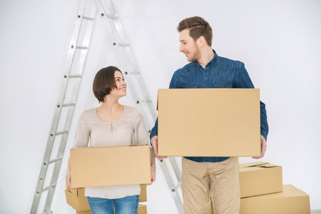 newly weds: Do everything together. Cheerful smiling loving couple holding boxes and expressing positivity while holding boxes Stock Photo