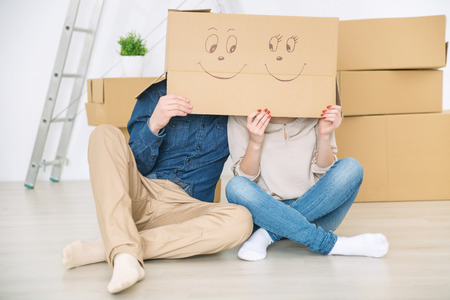 newly weds: Time for each other. Pleasant loving couple sitting on the floor and hiding under the box while having fun