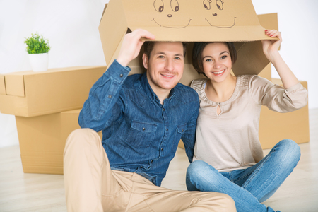newly weds: Involved in fun. Cheerful overjoyed young couple sitting on the floor and hiding under the box while smiling