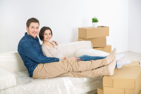 vivacious: Have some rest. Positive smiling vivacious couple sitting on the sofa and bonding to each other while resting Stock Photo
