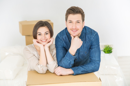 newly weds: Ready to work. Pleasant smiling young couple leaning on the boxes and holding hands on the chins while feeling happy Stock Photo