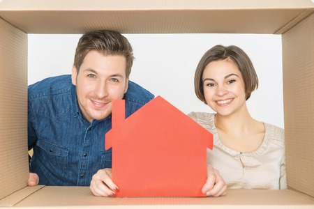 dwelling: Our new dwelling. Pleasant cheerful smiling couple holding figure of little house and expressing gladness while looking through the box
