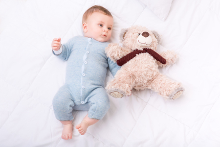 lactante: Niño con un juguete. El pequeño bebé está acostado en la cama y agarrando un juguete, mientras que mirando a un lado.