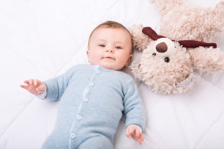 tots: Happy baby. Little baby boy is lying in bed with teddy bear at his side.