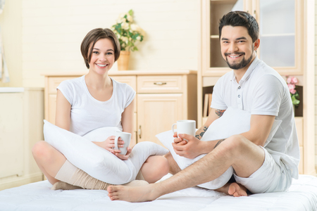 some: Get some energy. Happy smiling loving couple drinking tea and holding pillows while sitting in bed Stock Photo