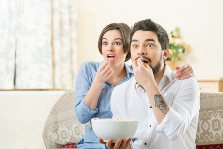 fresh pop corn: Full of emotions. Cheerful surprised loving couple eating pop corn and watching televising while bonding to each other