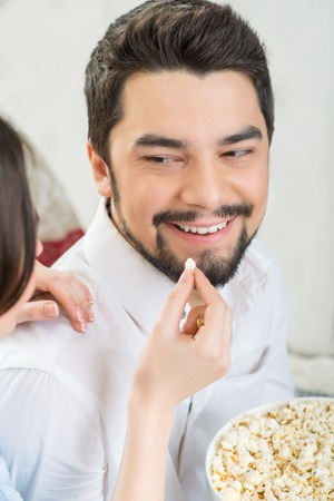 fresh pop corn: Taste it. Close up of happy woman feeding her husband with pop corn while eating it together and watching television Stock Photo