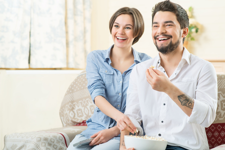 fresh pop corn: Full of joy. Cheerful delighted smiling couple sitting on the sofa and watching television while eating pop corn Stock Photo
