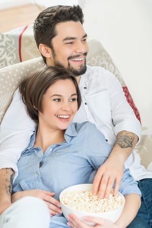 Avere un po 'di tempo libero. Primo piano di contenuti allegro giovane coppia di legame gli uni agli altri sul divano e mangiare pop corn mentre si guarda la TV