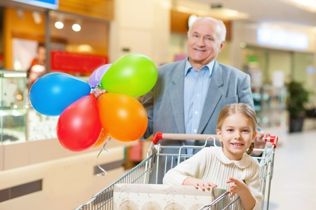 Holiday feeling. Grandfather is holding balloons and walking around the store with his lovely grandchild.