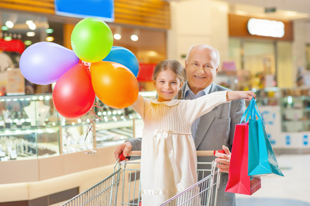 obtaining: Ready for celebration. Shot of granddaughter and grandfather finishing shopping together and obtaining things. Stock Photo