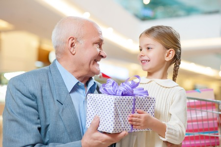grandkid: Giving love. Shot of wonderful grandkid making a present for nice grandfather. Stock Photo
