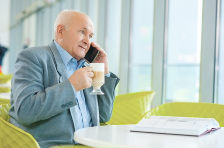 solicitous: Relaxing conversation. Old nice-looking man is talking on smartphone and enjoying his drink at the cafeteria.