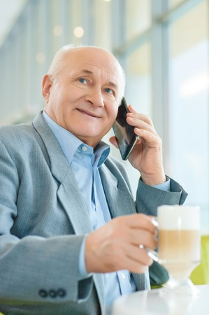 pleasurable: Pleasurable time of day. Caring grandfather is calling his adorable granddaughter, while sitting at the cafeteria and drinking coffee.