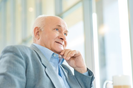 solicitous: Thoughts about life. Old man is holding his hand at face and staring straight while thinking.