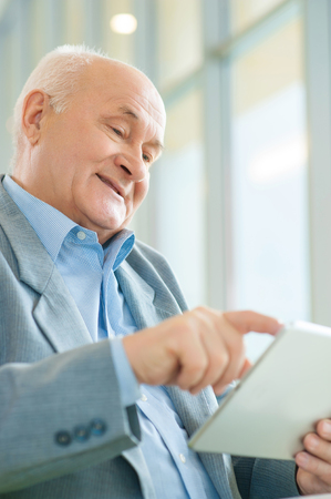 solicitous: Modern technologies. Close-up shot of nice-looking interested old man staring at tablet and using it. Stock Photo