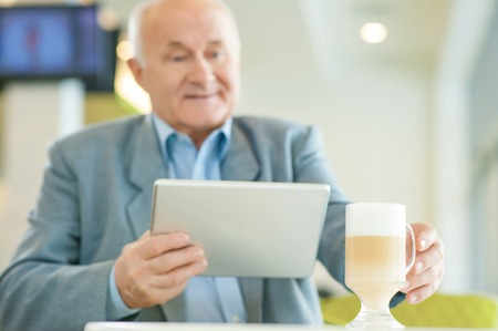 attentiveness: Relaxing time. Shot of mature concentrated man with laptop, taking coffee mug at the cafeteria. Stock Photo