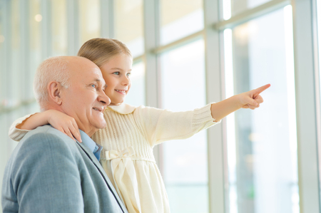 getting better: Getting to know world better. Curious little girl is pointing out to something interesting and asking her wise grandfather questions. Stock Photo