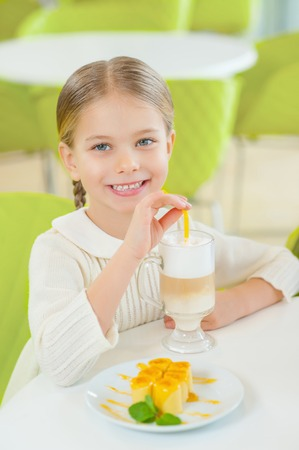 gladly: Having lunch.  Wonderful little girl is sitting at the cafeteria and gladly enjoying her meal. Stock Photo