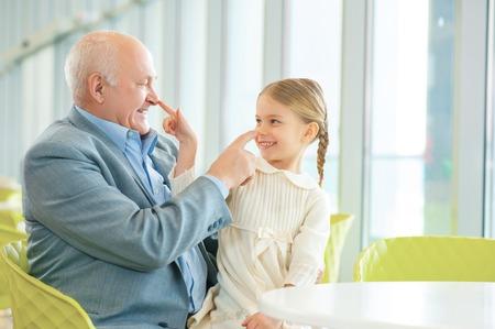 Láska a štěstí. Lovely vnučka se baví při splnění úsměvem šťastný dědeček v kavárně.