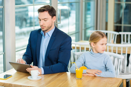 lack: Lack of attention. Young busy father using a tablet while his little daughter sitting aside and looking gloomily. Stock Photo