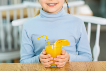 orange juice: Good for health. Close up shot with selective focus of girl holding her favorite orange juice.