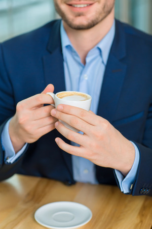 goodlooking: Close-up shot with selective focus of good-looking smiling man holding a cup of coffee. Stock Photo