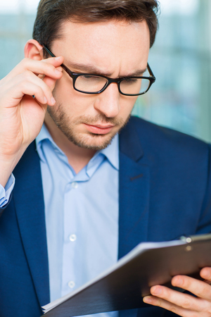 important information: Important information. Young nice man is holding glasses and exploring papers with concerned look Stock Photo