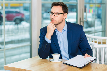 businessman thinking: Running business. Handsome businessman sitting at the cafeteria and thoughtfully looks aside while holding documents.