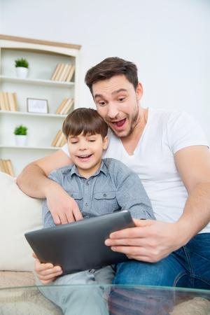 asombro: Se divierten juntos. Papá está mostrando hijo algo muy excitante en la tableta y haciéndolo reír.