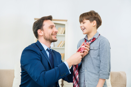 knotting: New dress code for business. Young handsome businessman is showing cheerful son style of real businessman while knotting tie