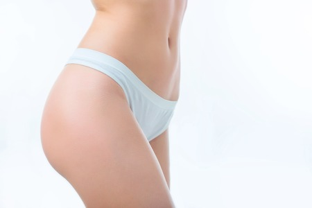 turned: Go in for sport. Close up of hip of slim woman staying half turned isolated on white background