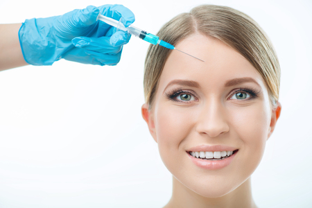 cosmetologist: Breath of youth. Portrait of cheerful beautiful woman smiling while professional cosmetologist making injection on white background